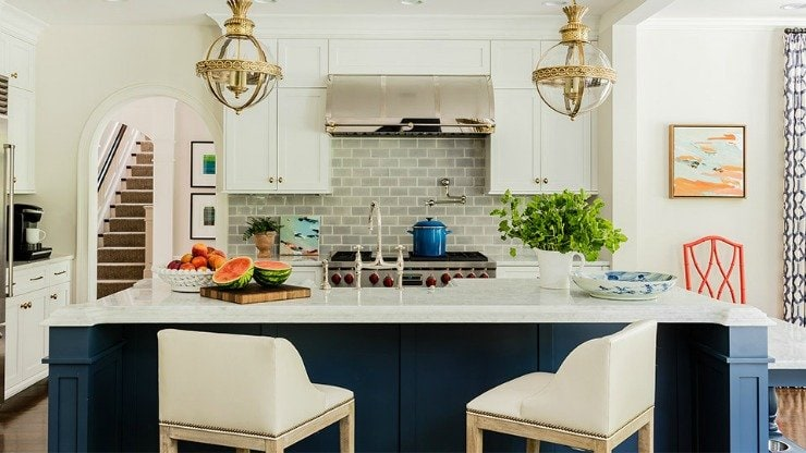 White kitchen with a navy blue island, blue subway tile back splash, and brass pendants. Designed by Katie Rosenfeld. Photo by Michael J. Lee