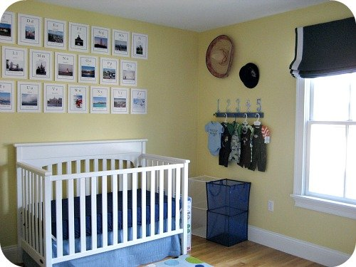 A blue and yellow nursery for a boy with white furniture and handmade art.