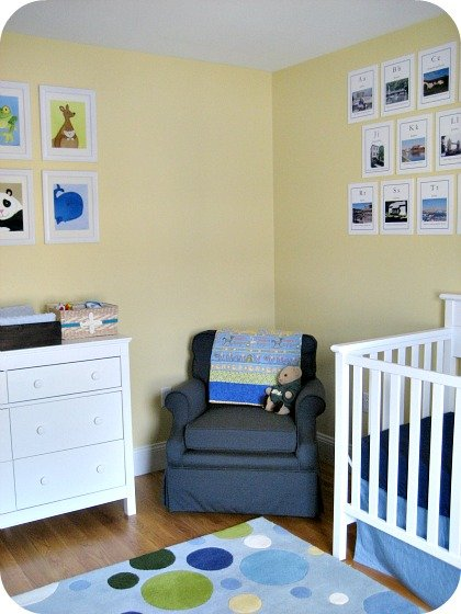 Blue and yellow boy nursery with a cozy blue rocker-swivel chair.