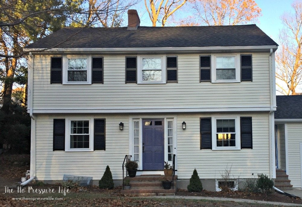 Garrison colonial exterior makeover. Cream with white trim, black shutters, and blue door.