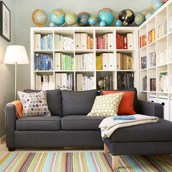 Corner sectional with bookcases behind it, via BHG.com