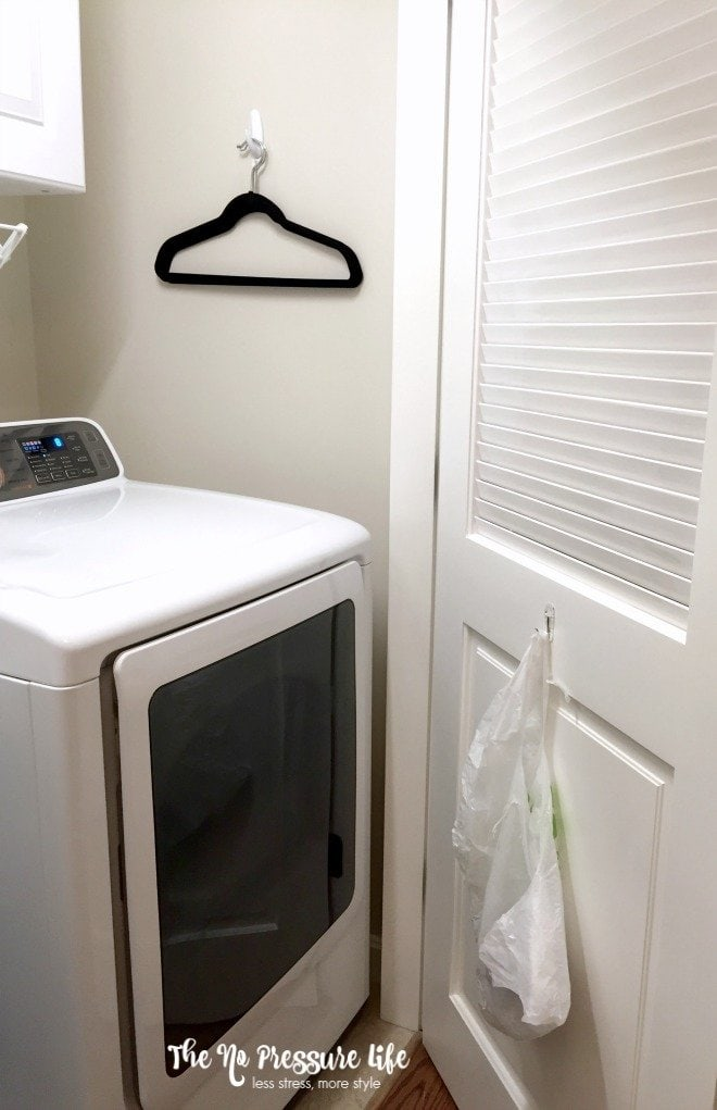 Quick laundry room organization tip: Hang a plastic grocery bag on a Command hook to throw away lint! Get more tips at The No Pressure Life.
