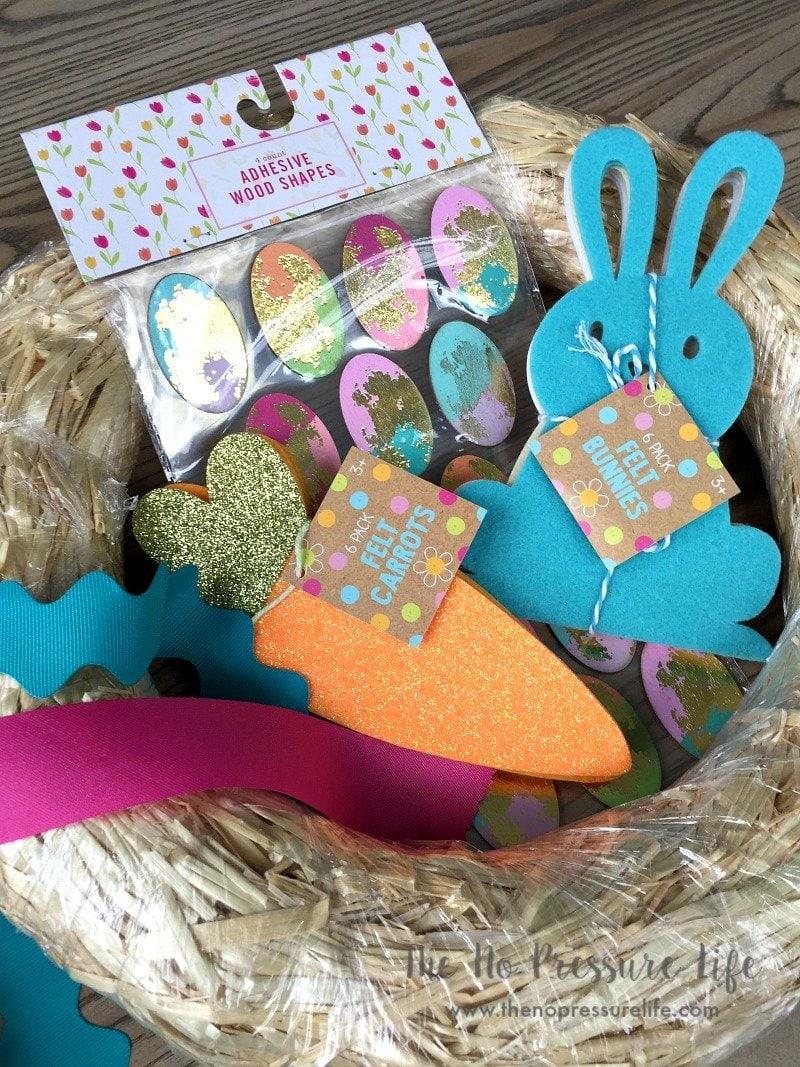 supplies to make a DIY Easter wreath - straw wreath form, egg stickers, ribbon, felt bunnies, felt carrots