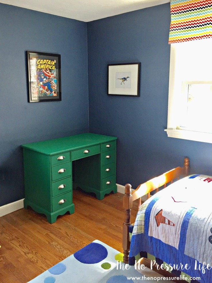 Boys bedroom with navy blue walls, green painted desk, and superhero art.