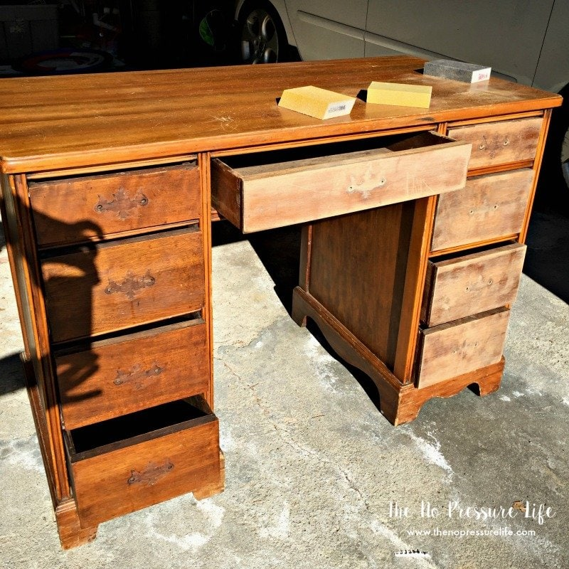 Brown wood thrift shop desk on a concrete floor with sanding blocks on top.