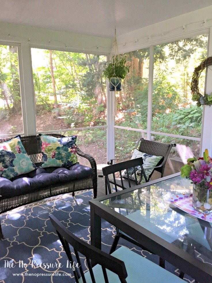 small screened-in porch decorated in navy and aqua