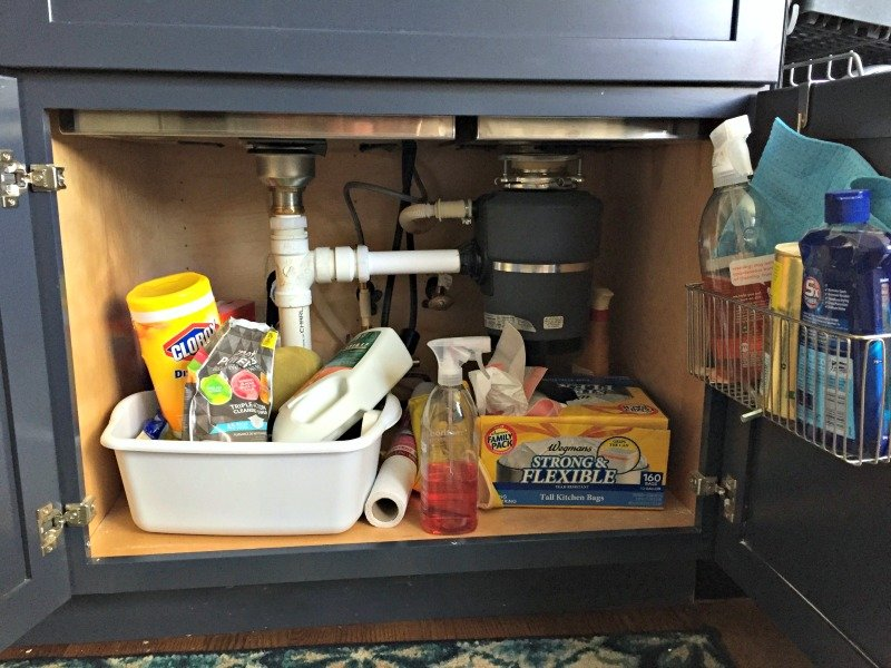 Messy cabinet under the kitchen sink before organizing and getting better storage solutions.