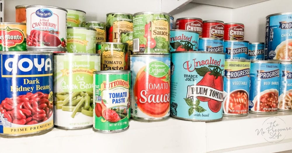 lots of canned food on an expandable tiered shelf organizer in a kitchen pantry
