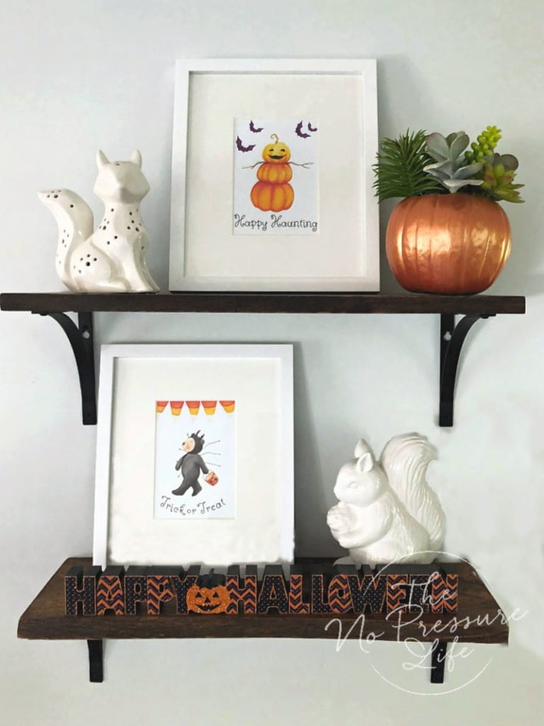 DIY faux succulent pumpkin painted copper on a shelf decorated for Halloween