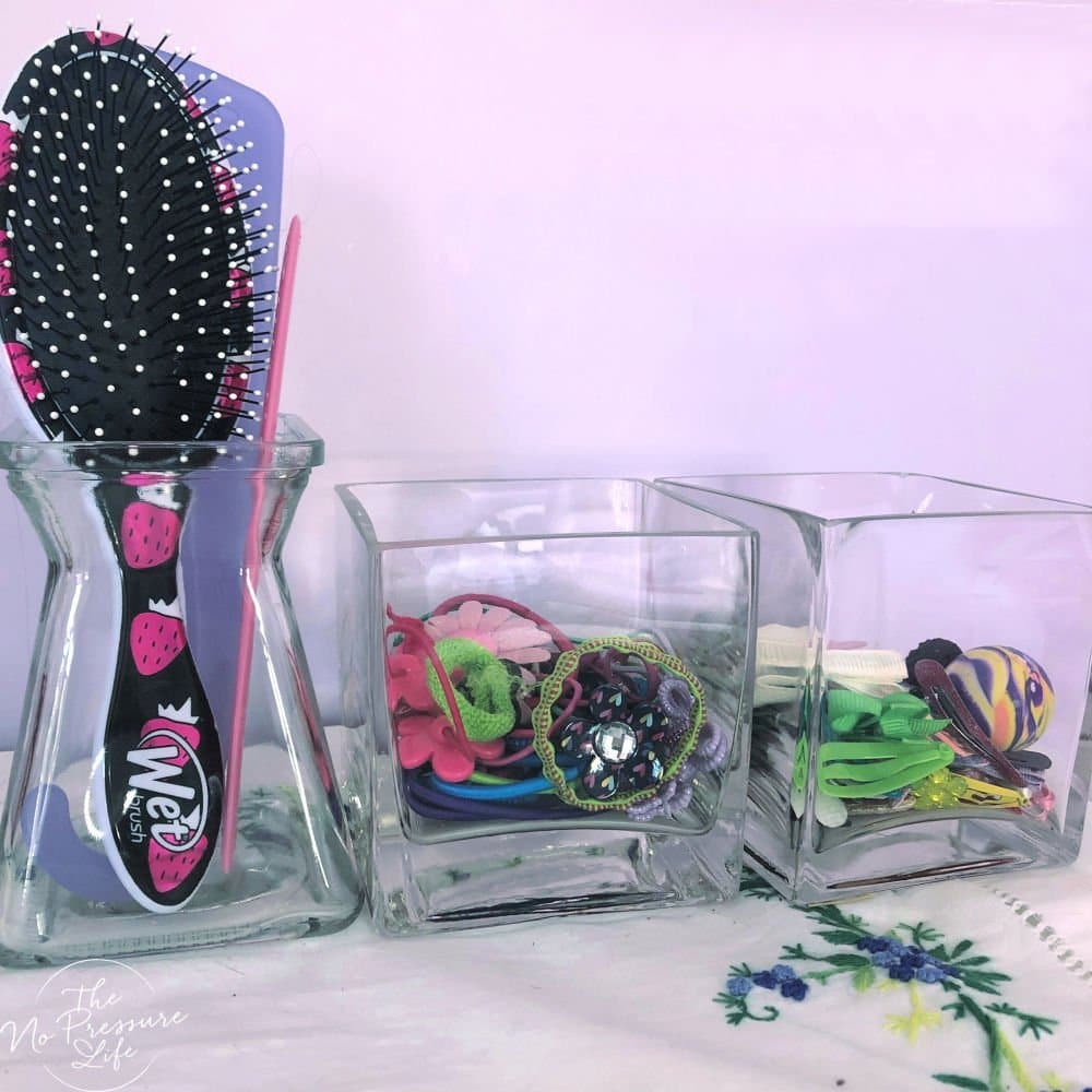 DIY hair accessory storage with brushes, elastics, and clips in glass vases