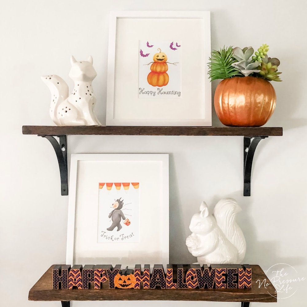 cute Halloween shelf decor with framed art and succulent pumpkin decoration