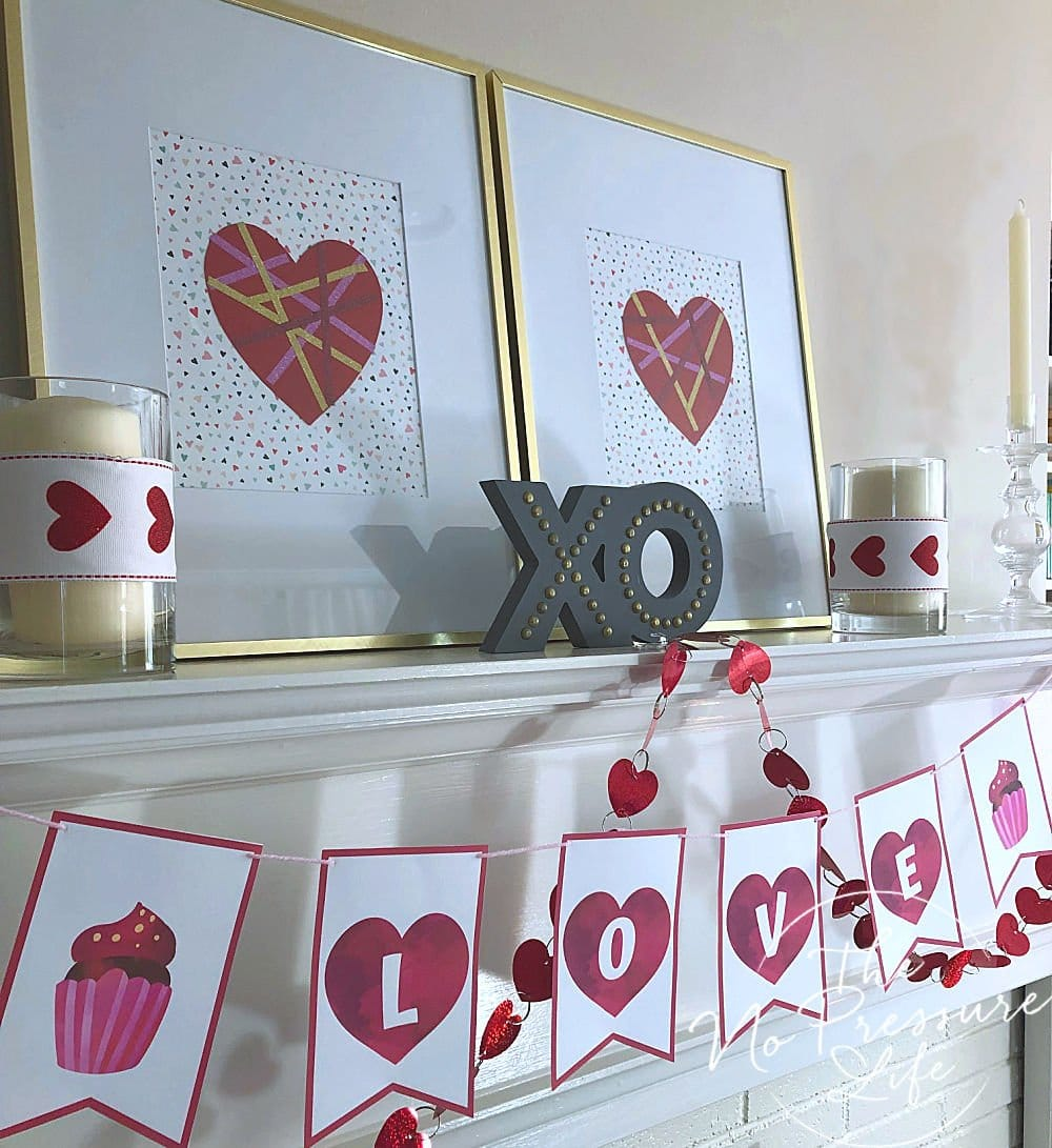 Mantel decorated for Valentine's Day with free printable LOVE banner with pink and red hearts.