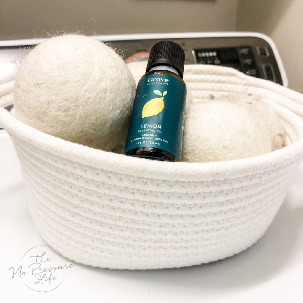 Wool dryer balls and lemon essential oil in a white basket - Beach towels and bathing suit on washing machine - Summer Laundry Tip